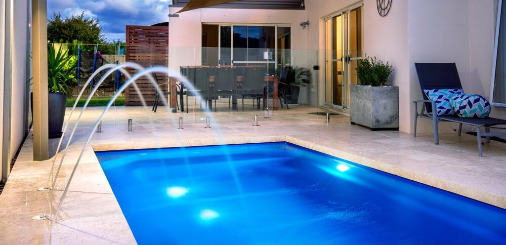 Backyard pool with a deck jet water feature